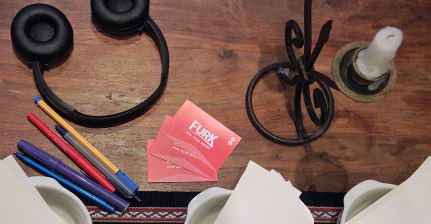 Photo d'un casque audio, d'une bougie et des cartes de visites de Furk