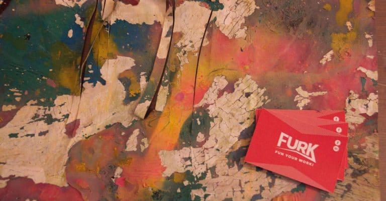 Photo d'un tableau abstrait aux multiples couleurs avec la carte de visite de Furk posée dessus